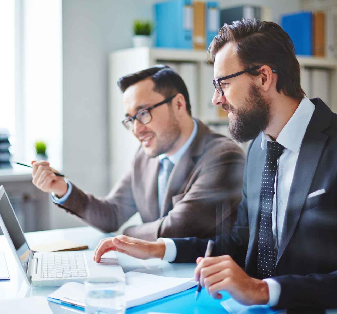 Zwei Männer die verschiedene KFZ-Versicherungen evaluieren.