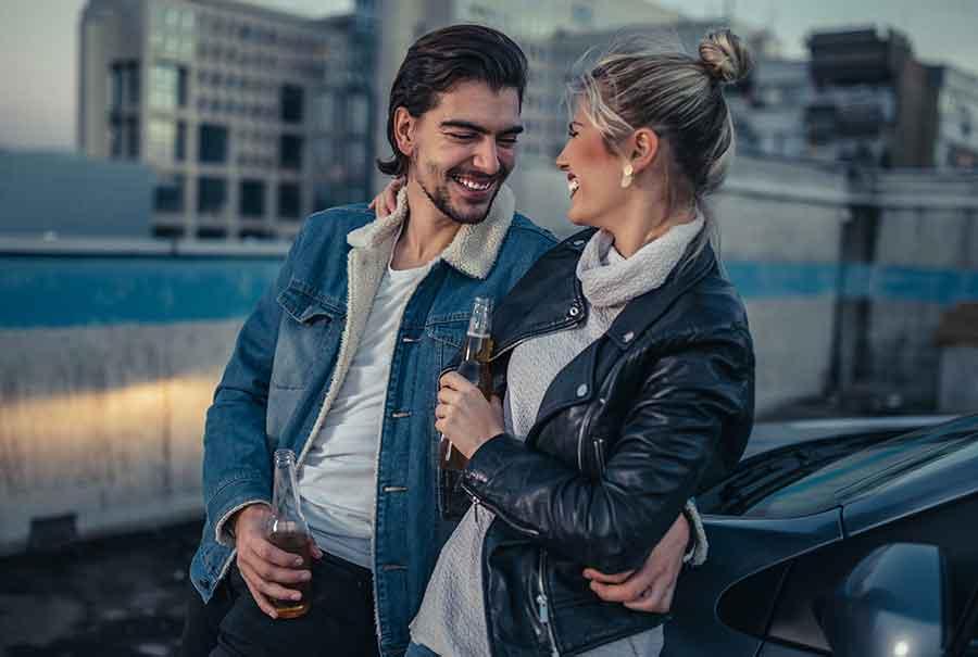 Pärchen feiert den Autokauf mit einem Bier.